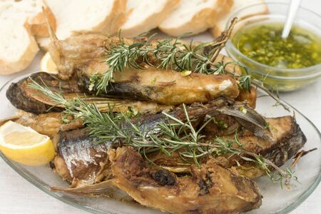Fried fish or baked carp with rosemary, lemon and garlic sauce is served with some bread.