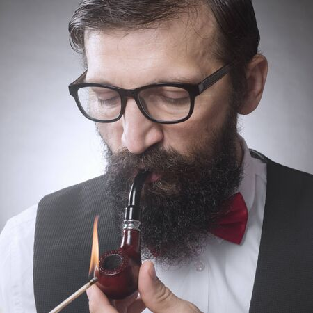 The bearded man with eyeglasses is igniting and smoking tobacco pipe. Foto de archivo