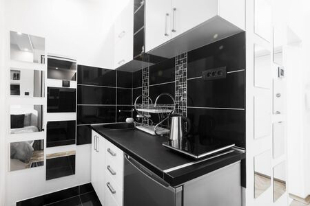 Black and white kitchen with new furniture, modern interior design in apartment.