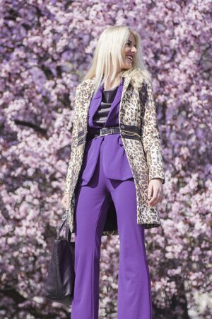 The attractive blond hair female fashion model in purple clothes is standing on floral background.
