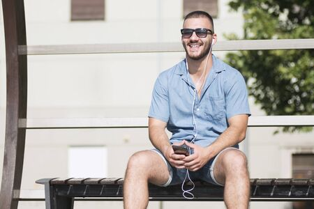 Smiling young guy with earphones is sitting on bench and using phone.