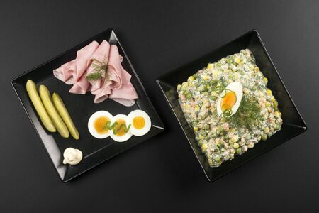 Luxury gourmet appetizer with Russian salad, ham, eggs and pickle on black background.