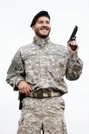 The smiling army soldier in military uniform is holding a pistol in hand on white background. Foto de archivo