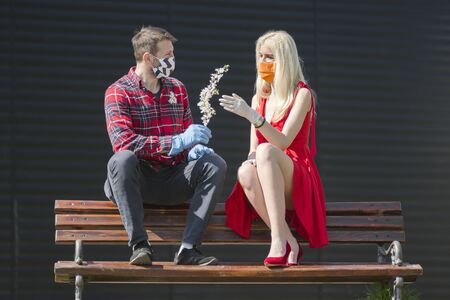 The man in protective mask is giving a flower to blond hair woman in red dress, sitting on the bench, modern love and romance in COVID19 season.