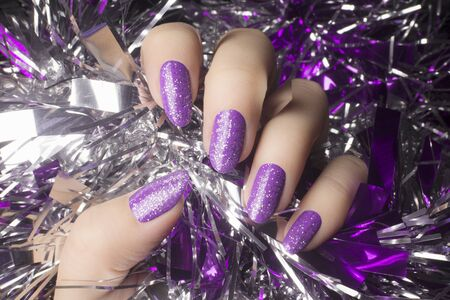 Female hand with glittered purple nails is holding silver decoration, manicure concept. Foto de archivo