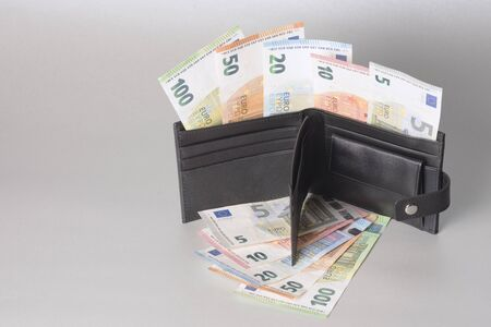 Euro banknotes in black purse on gray background.