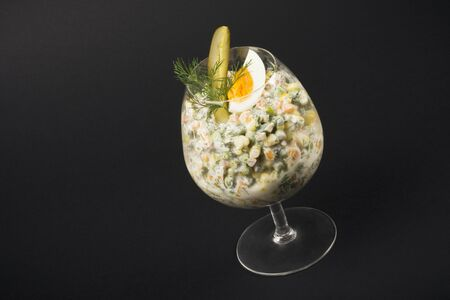 Russian salad served in drinking glass on black background.