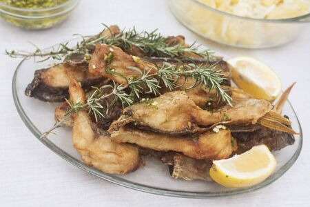 Served fried fish with rosemary and lemon on white.