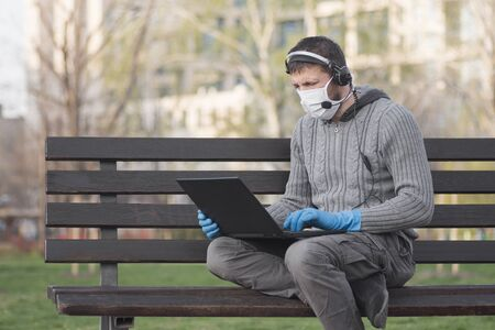 The man in protective mask and gloves with headphone is using laptop outdoors, sitting on bench in the park. Foto de archivo