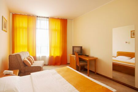 Lovely simple hotel room interior design with orange decoration.