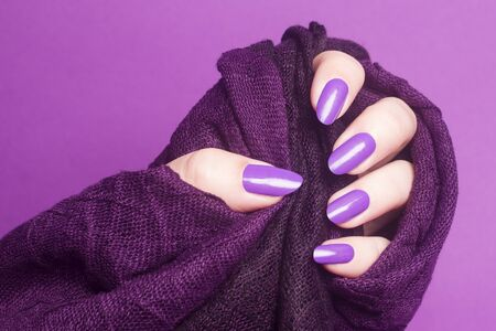 Female hand with pink purple nails is holding purple textile on pink background, manicure and nail care concept.