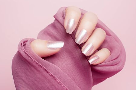 Female hand with beautiful shiny pink nails on bright pink background.