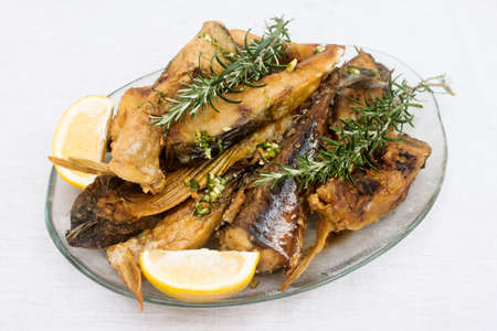 Fried fish with lemon and rosemary on plate on white background.