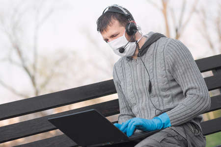 The male freelancer in protective mask and protective gloves with headphone and microphone is working on laptop Foto de archivo