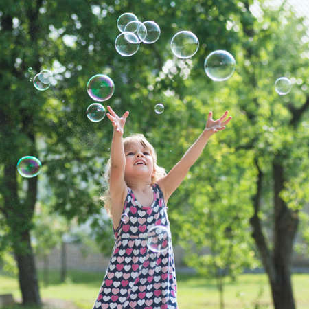 The cute little girl in dress is playing with soap bubbles outdoors.