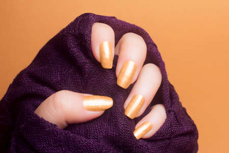 Female hand with beautiful gold colored nails in purple clothing on orange background, manicure concept. Foto de archivo