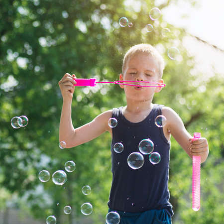 The cute blond hair boy is blowing soap bubbles outdoors. 写真素材