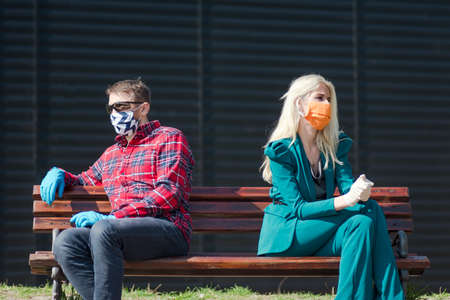 The man and woman in protective masks and gloves are in social distancing while sitting on the bench during coronavirus pandemic.