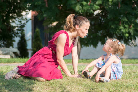 The mother in red dress is playing with her cute daughter outdoors on the grass, togetherness and family.