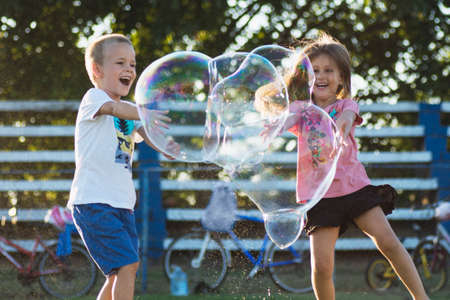 Happy children are playing with giant soap bubbles outdoors, joyful childhood concept. 写真素材