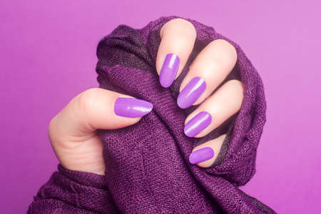 Female hand with purple or pink nails is holding purple textile on pink background, manicure and nail care concept.