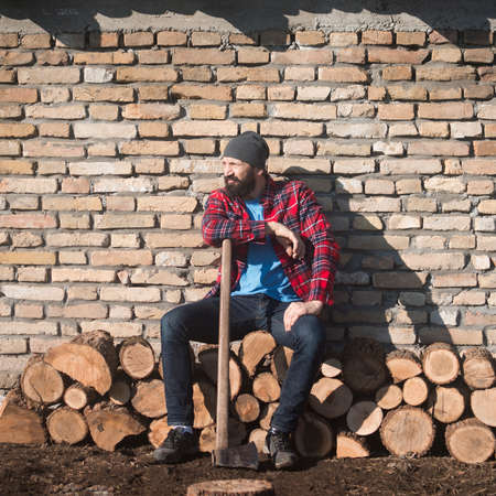 The tired lumberjack is sitting and resting in front of brick wall, worker in rural scene.
