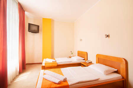 Simple lovely hotel room with two beds, interior design for accomodation.