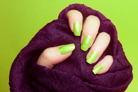 The female hand with neon green nails is wearing a purple fabric on green background, manicure and nail care concept.