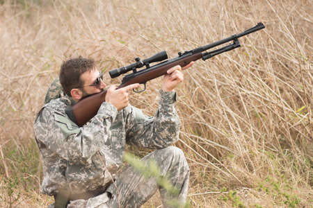 The hunter in military uniform is aiming and shooting a weapon with sniper in dry bush. Stock Photo