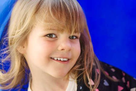 Portrait of cute smiling little girl on blue 写真素材