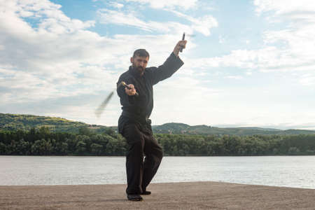 The bearded man in black kimono is practicing ninja style in martial arts with two nunchuks outdoors in the nature.