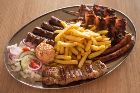 Fast food meal with mixed meat, french fries and vegetable garnish on plate.