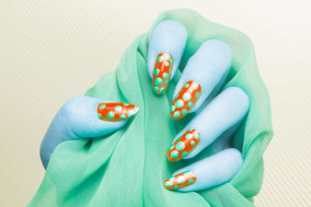 Blue female hand with green spotted red nails is holding green fabric on yellow striped background, manicure and nail art concept.