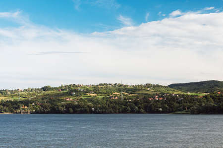 Beautiful hilly landscape with Danube river in Serbia on cloudy sky background.