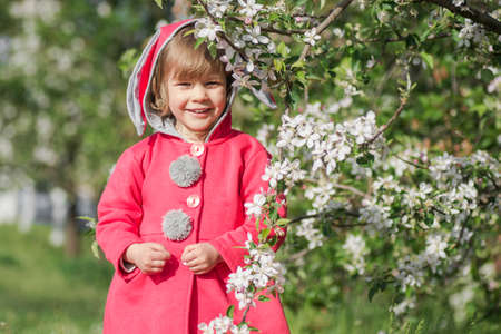 Smiling cute little girl in red coat is standing outdoors with blooming branch. 写真素材