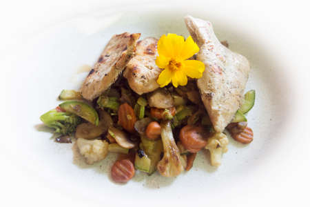 Turkey meat meal with grilled vegetables is served on white plate and decorated with flower.