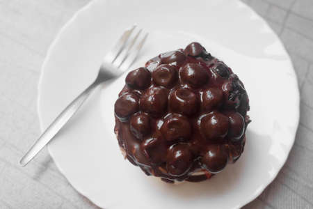 Delicious fruity chocolate cake with sour cherry on white plate with fork.
