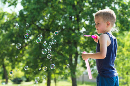 The cute six years old blond hair boy is blowing soap bubbles and playing with them outdoors.