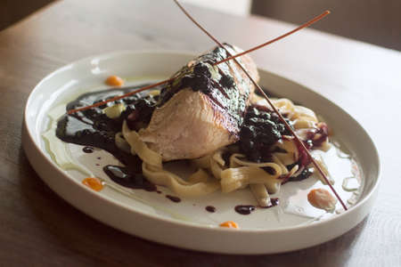 Luxury dinner meal in restaurant, turkey meat with blueberry sauce and pasta, meat with sweet sauce.