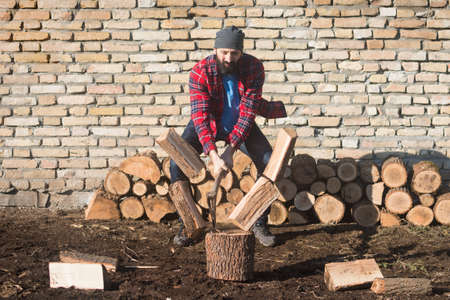 The bearded lumberjack worker is cutting firewood with axe on brick wall