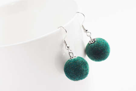 Green pearl earrings jewelry is on white background.