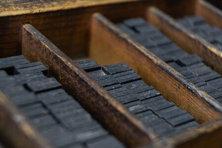 Printing press letter blocks in a wooden shelf.