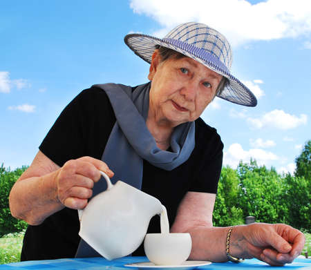 The senior woman pours milk from a jug in a mug Stock Photo - 9375739