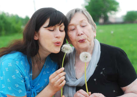 grand daughter: Happy grandmother and grand daughter with dandelions on the meadow Stock Photo