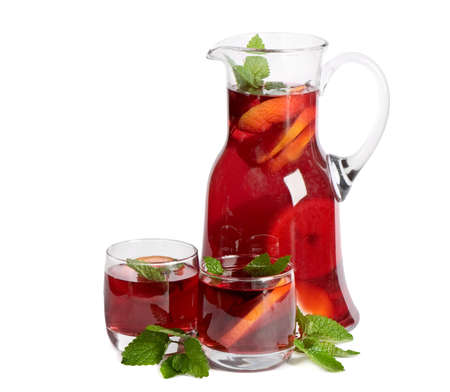 Fruit drink in jug and two glasses. Isolated on white