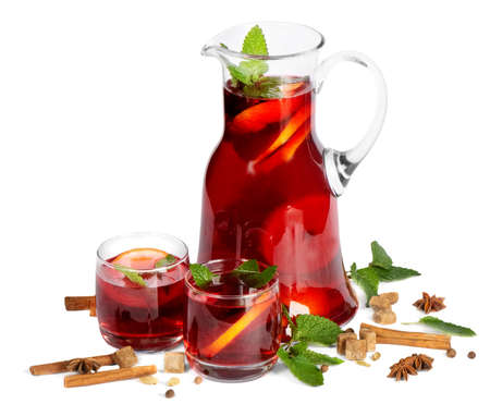 Fruit drink in jug and two glasses. Isolated on white  photo