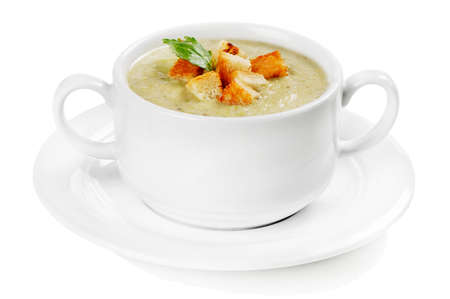 Creamy soup with croutons isolated on white background