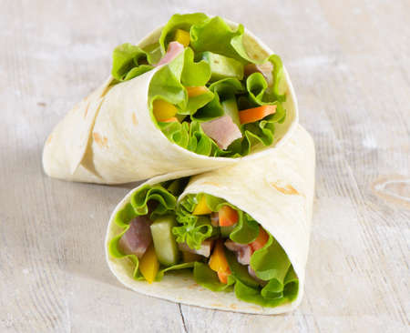 Fresh wrap sandwiches filled with ham, lettuce and pepper Stock Photo