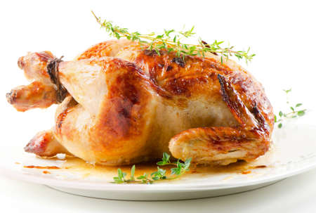 Roasted chicken on white plate with thyme Stock Photo