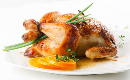 Roasted chicken on white plate with orange